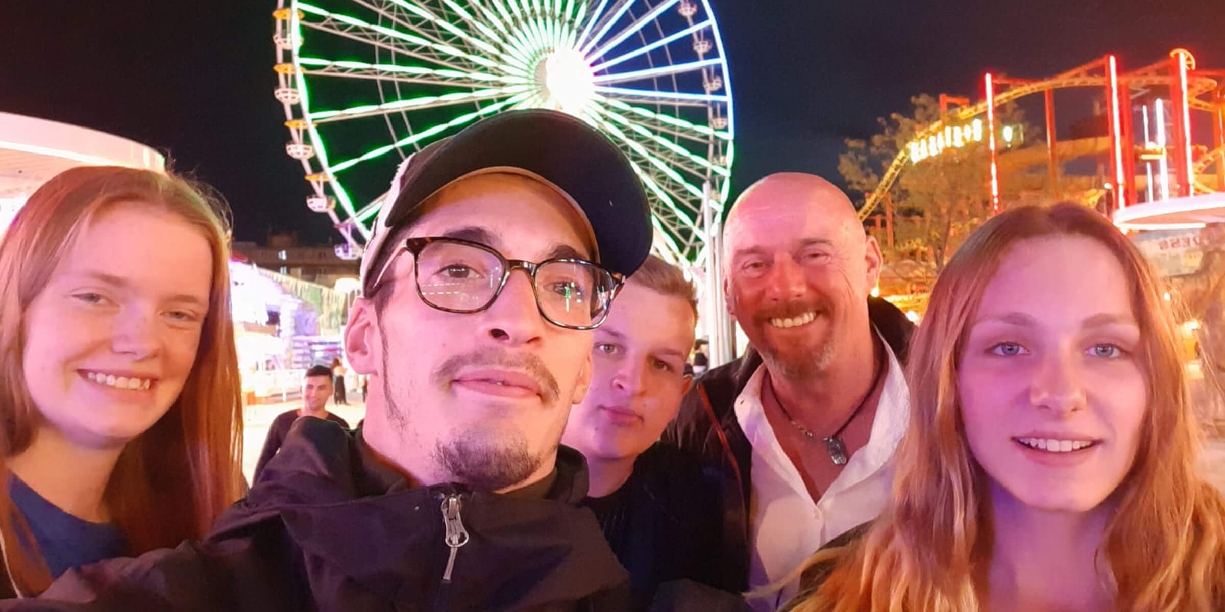 Nachtsituation, im Hintergrund ein Riesenrad. Im Vordergrund stehen junge Teilnehmende und ein Ausbilder und lächeln in die Kamera