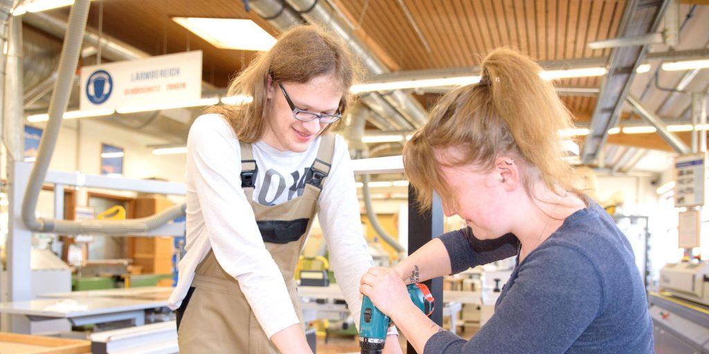 Zwei Teilnehmer werken an einem Stück Holz