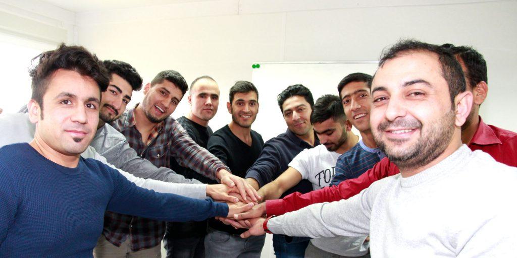 Eine Gruppe ausländische Teilnehmer streckt die Hände in der Mitte zusammen