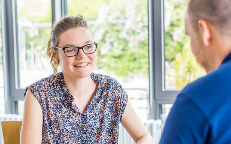 Gesprächssituation am Tisch, junge Frau lächelt ihren Gesprächspartner an, das nur von hinten angezeigt wird