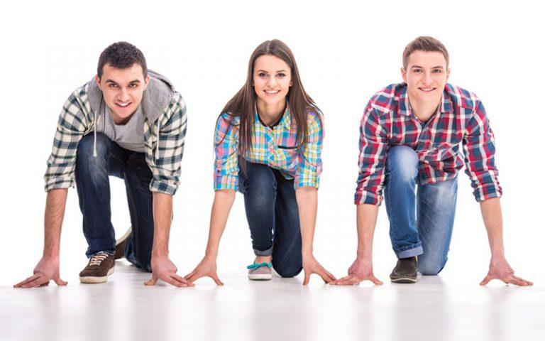 Drei junge Menschen knien in Startposition auf dem Boden und lächeln in die Kamera