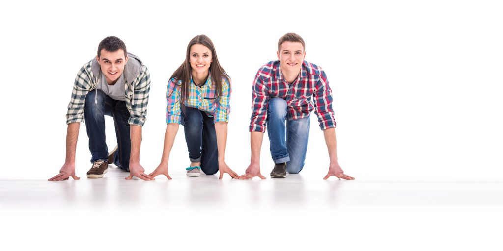 Drei junge Menschen knien in Startposition auf dem Boden