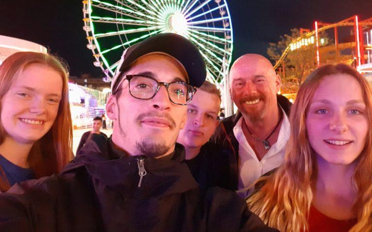 Bild bei Nacht mit einem Riesenrad im Hintergrund. Vorne stehen Teilnehmende und ein Ausbilder und lächeln in die Kamera