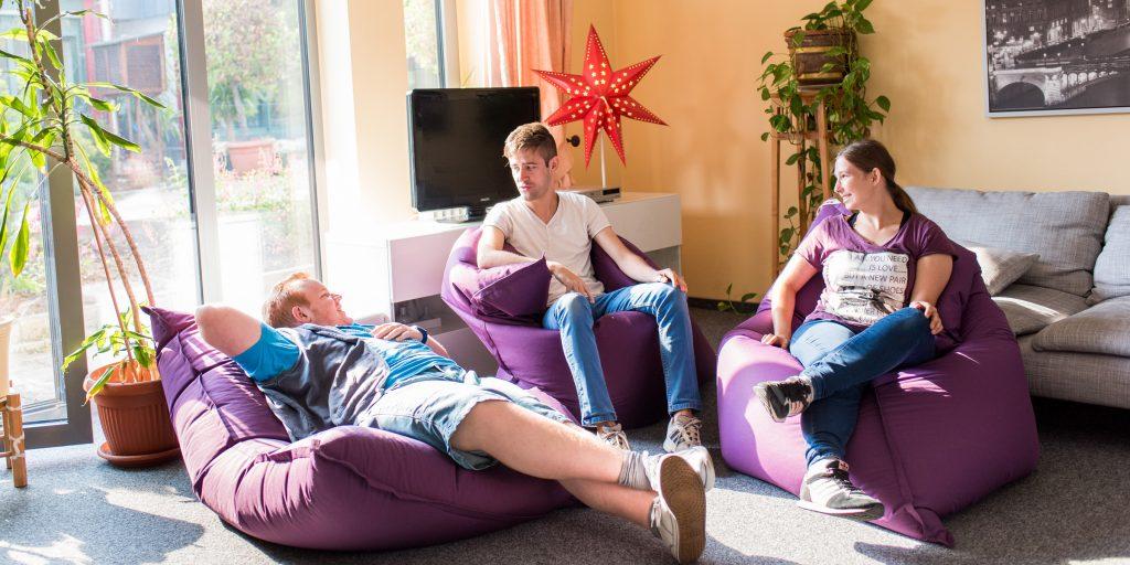 Drei Teilnehmende liegen auf Sitzsäcken im Wohnbereich