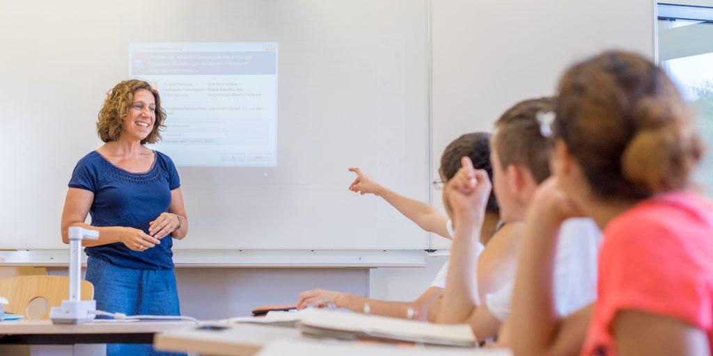 Lehrperson steht vor Schüler*innen und lächelt