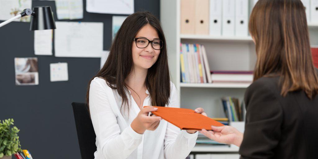 Junge Teilnehmende überreicht ihre Bewerbungsmappe an eine andere Person