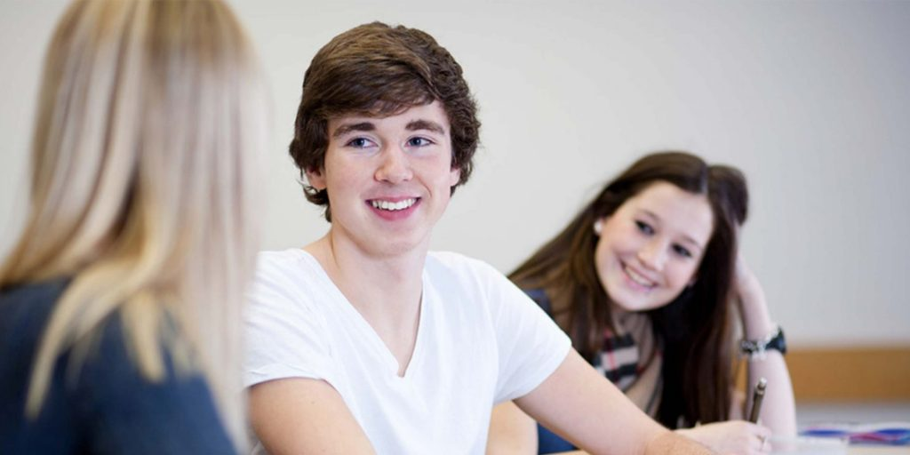 Drei Jugendliche schauen sich an