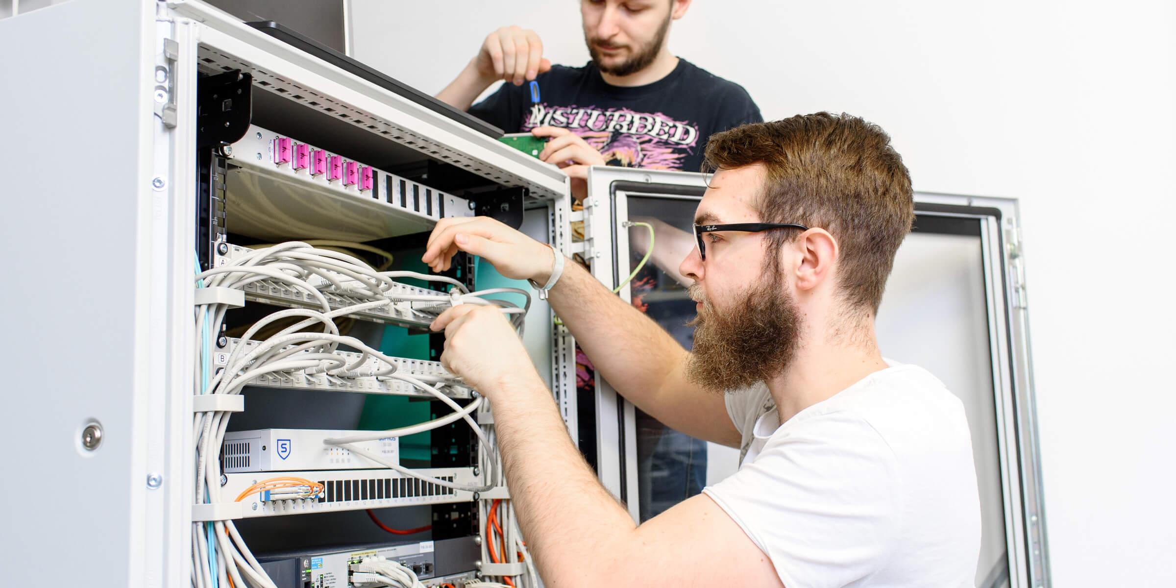 Zwei junge Männer stehen an einem Server durch