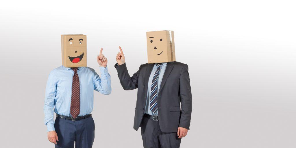 2 Männer in Anzügen mit Pappkarton auf dem Kopf erheben beide die Finger - neue akademie Seminare