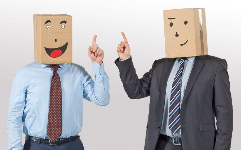 Zwei Männer mit Hemd, Schlips, Anzug und Pappkarton auf dem Kopf halten beide die Zeigefinger nach oben - neue akademie - bbw Südhessen