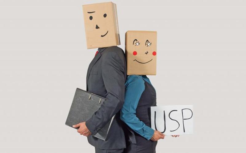 Mann und Frau in Anzügen mit Pappkartons auf dem Kopf: Mann hält Akte im Art, Frau ein Schild mit USP - neue akademie - bbw Südhessen