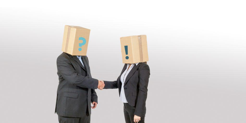Mann und Frau mit Anzug und Pappkarton auf dem Kopf reichen sich die Hände - neue akademie bbw Südhessen