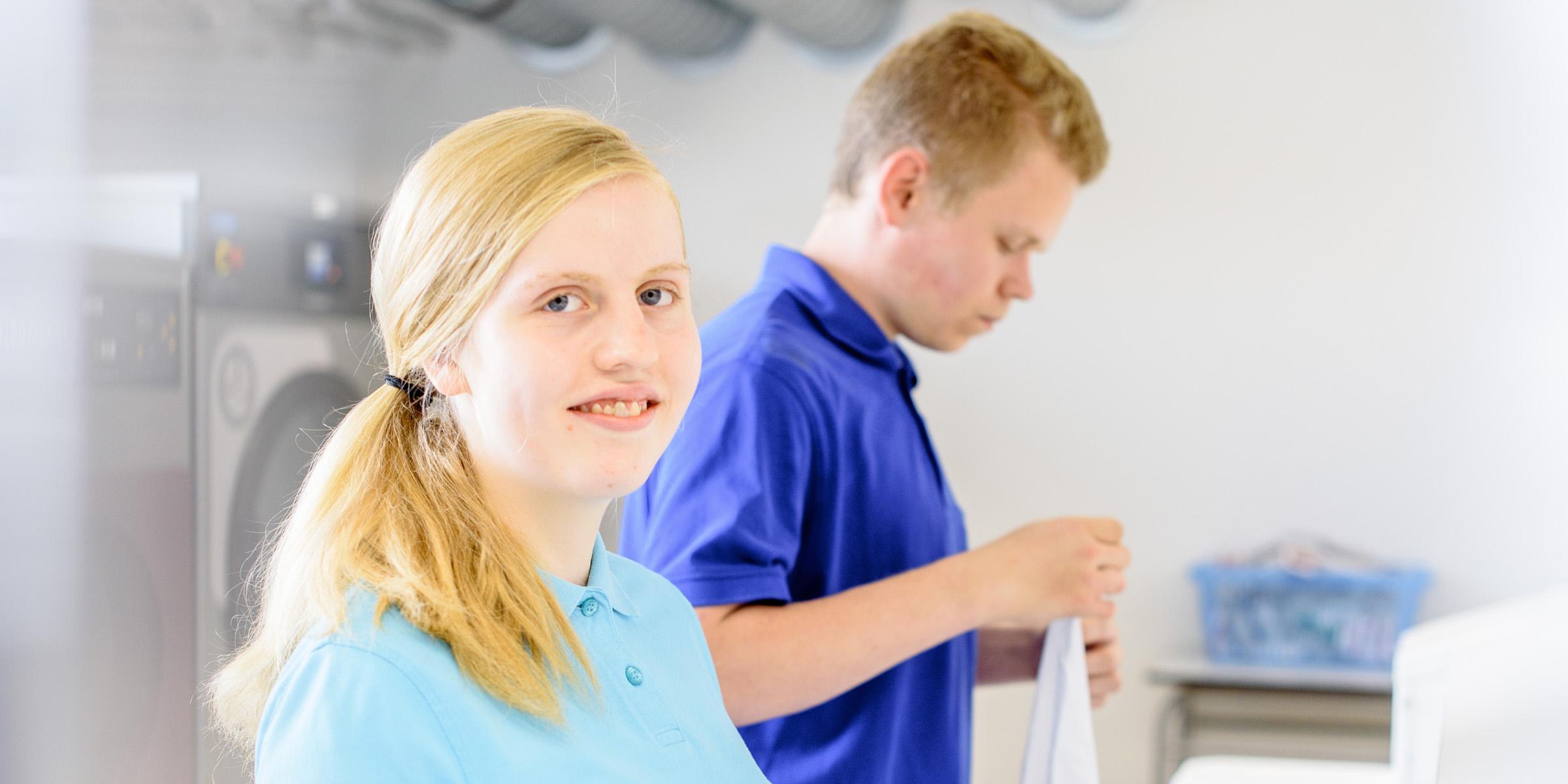 In der bbw Südhessen Textilreinigung arbeiten junge Frauen und auch junge Männer. Hier sehen sie bbw-Azubis beim Falten von Wäsche