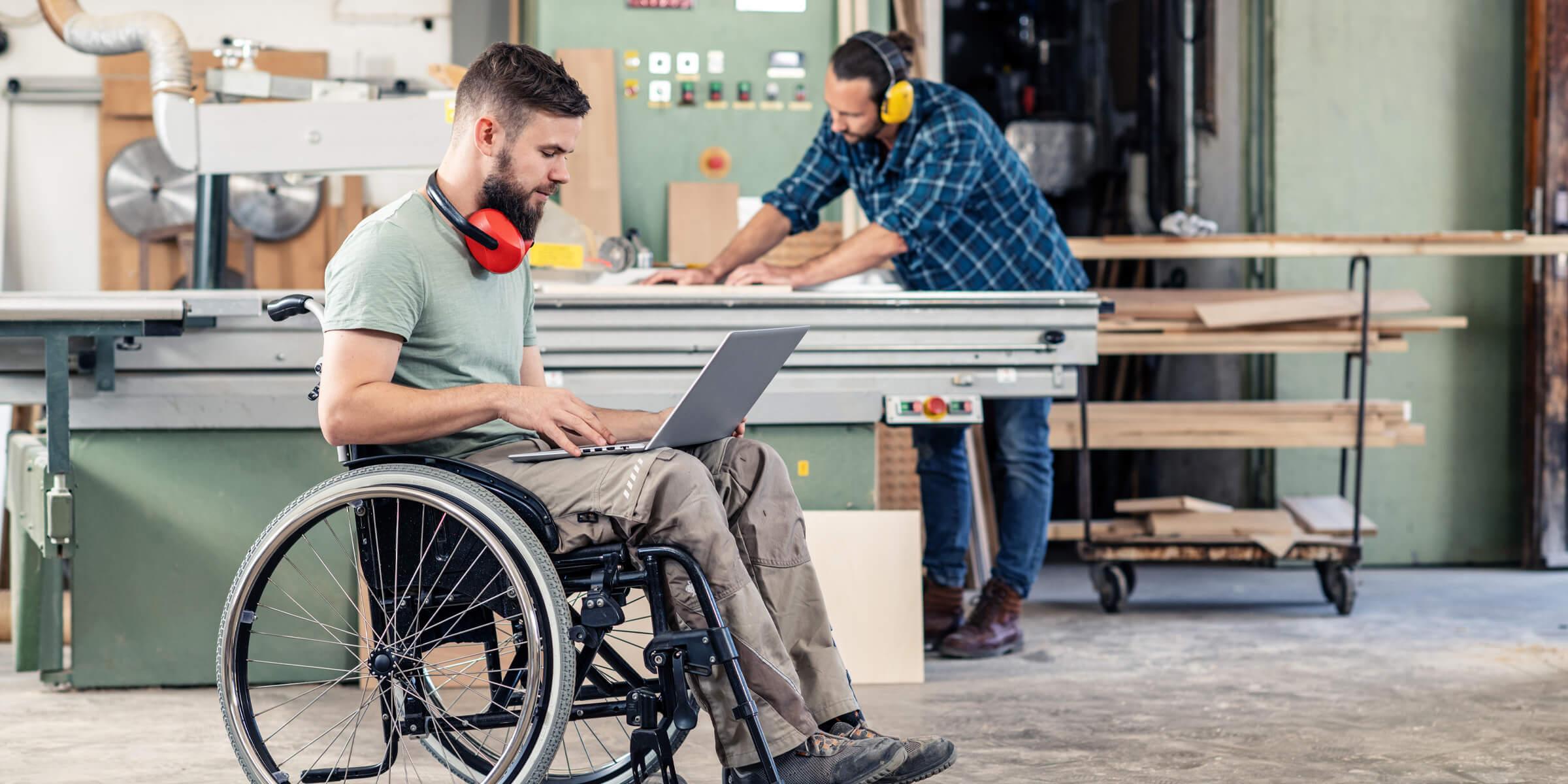 Junger Mensch sitzt im Rollstuhl und schaut in seinen Laptop, im Hintergrund sieht man, dass er in einer Werkstatt ist und ein anderer junger Mensch dort an einer Werkbank mit Holz arbeitet