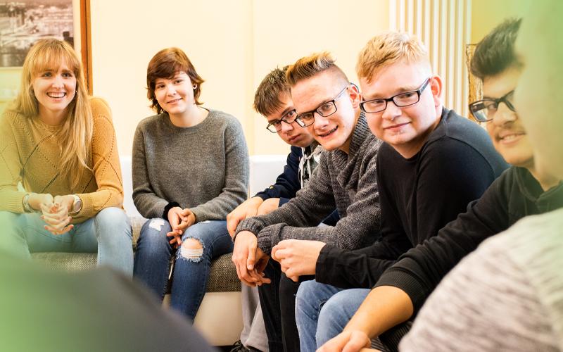 Jugendliche aus der Kinder- und Jugendhilfe sitzen zusammen