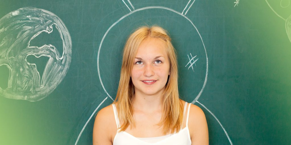 Jugendliche steht vor einer Tafel mit Planeten bemalt und lächelt - symbolisch für die Möglichkeiten in unseren Welträumen der Jugendhilfe
