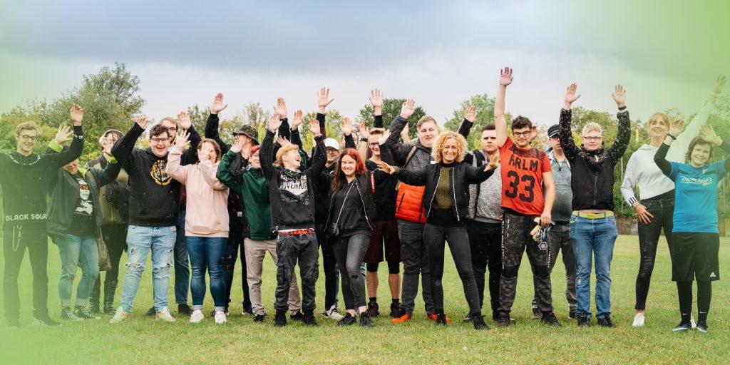 gruppe junger Menschen nebeneinander auf Wiese reißen Hände in die Höhe - wohnen in der jugendhilfe bbw südhessen