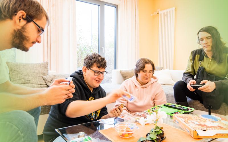 Gruppe Jugendlicher sitzen im Wohnzimmer am Tisch und spielen - Jugendhilfe bbw Südhessen