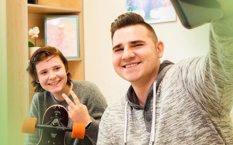 2 Jugendliche machen ein Selfie mit dem Handy in der Jugendhilfe des bbw Südhessen
