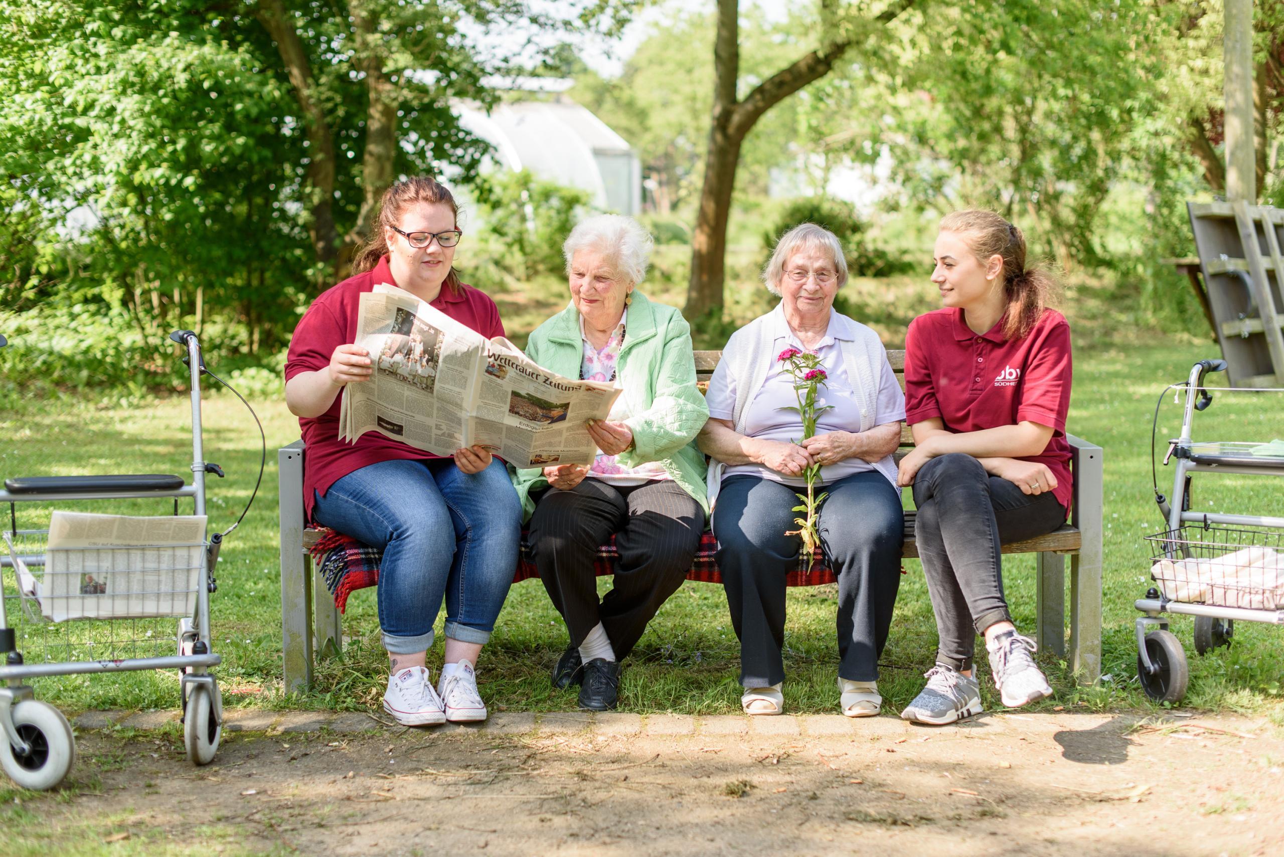 Azubis der Altenpflegehilfe mit 2 Damen aus dem Pflegeheim auf einer Bank sitzend