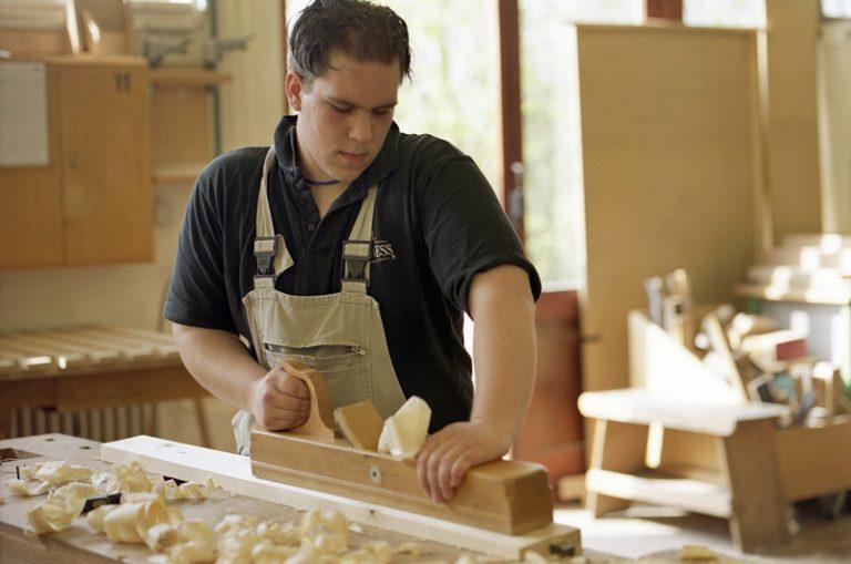 Junger Mann hobelt Holz in der Holzwerkstatt