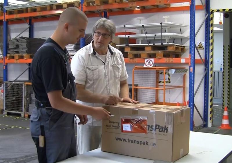 Azubi der Lagerlogistik steht mit Ausbilder an einem Paket in der Lagerhalle
