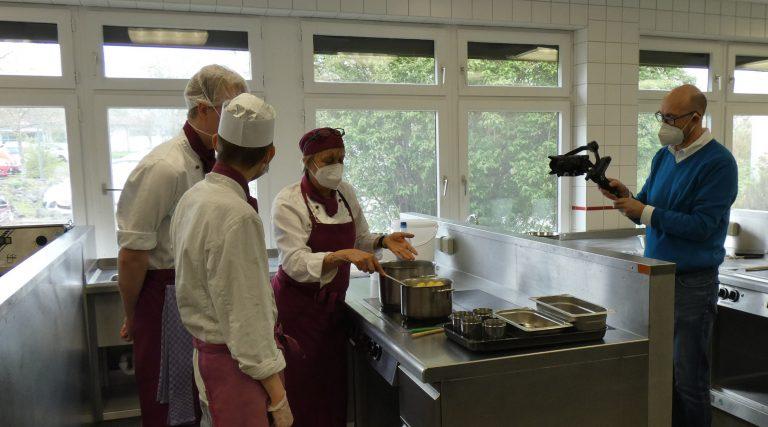 Filmer beim Filmen des neuen Infotage-Films im bbw Südhessen in der Lehrküche mit Ausbilderin und Azubis