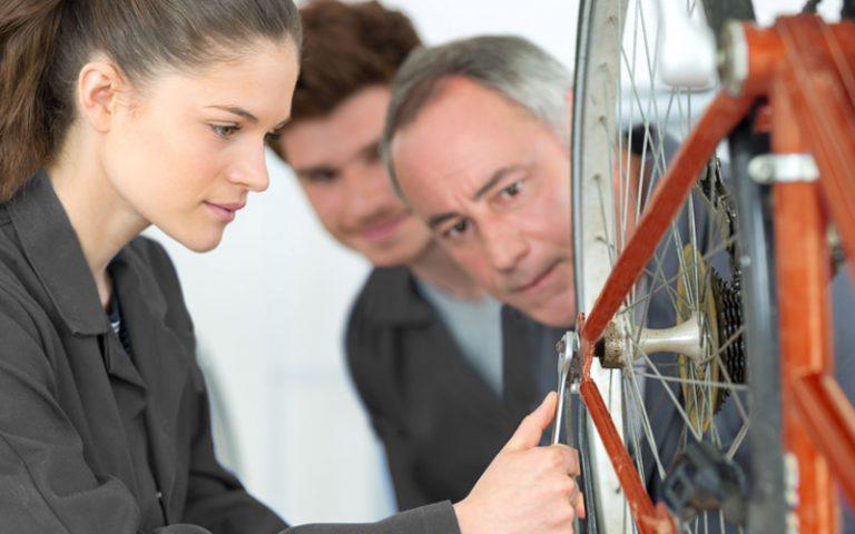Fahrradmonteur arbeitet mit zwei Azubis an einem Reifen vom Fahrrad - Ausbildungangebot Fahrradmonteur im bbw Südhessen